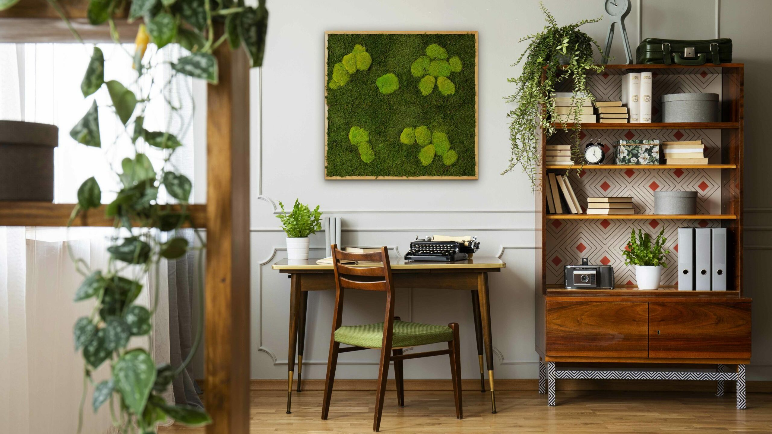 Ein Moosbild hängt in einem Hipster Home Office mit einer schwarzen Retro-Schreibmaschine auf einem einzigartigen Holzschreibtisch, ein moderner Stuhl aus der Mitte des Jahrhunderts und ein renoviertes Bücherregal