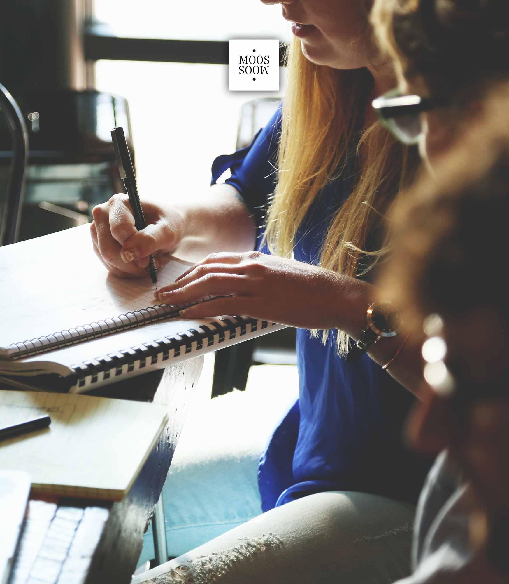 junge, blonde Frau macht sich auf einem Blatt kreative Notizen