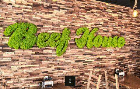 Logo des Restaurants Beef House aus apfelgrünem Islandmoos als Referenzbildan einer Ziegelwand