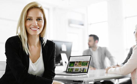MoosMoos Verkäuferin sitzt am Konferenztisch mit aufgeklapptem Laptop und lächelt